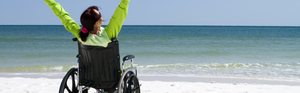 image shows a wheelchair user with their arms raised to demonstrate triumph on a beach