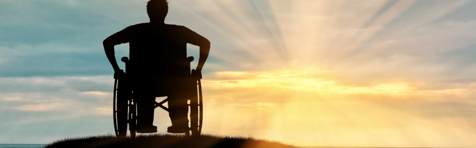 image shows a silhouette of a wheelchair user on top of a mountain